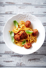 Linguine with meatballs, tomato sauce and basil leaves