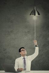 Attractive businessman pulling a bright lamp
