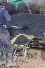 Asphalt workers with a shovel filling wheelbarrow with asphalt