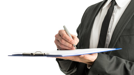 Side view of a businessman signing legal papers on a map with fo