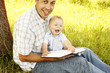 young father with a young son reads the Bible