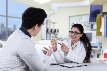 Female dentist explaining pill to patient