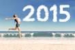 Hispanic woman leaping at beach