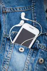headphones and smartphone in the pocket old denim jacket