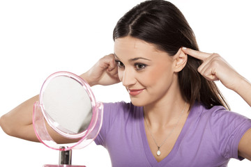 smiling girl touching her ears with the fingers in the mirror
