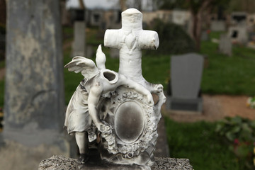 Headless angel. Destroyed tombstone at the abandoned cemetery.