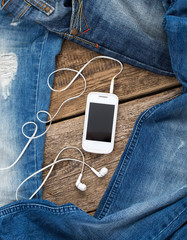 Jeans around mobile smartphone with earphones on old wooben back