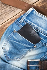 blue jeans pocket with Wallet black on wooden background