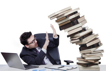 Male manager with falling books on desk