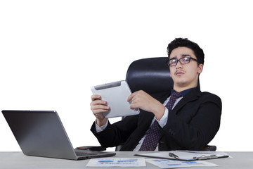 Male worker holding a tablet at desk