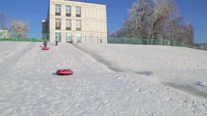Children ride on the icy hill in winter