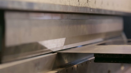 Machine flexes metal sheet