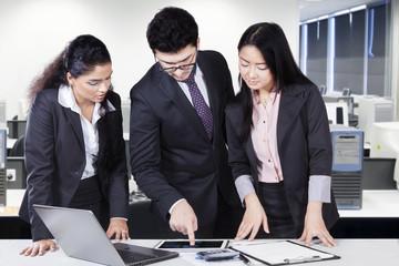 Team leader showing chart on tablet