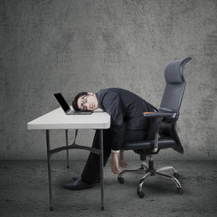 Tired worker sleeping on laptop at desk