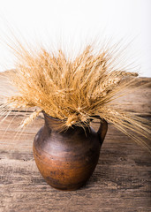 Rye spikelets in old pot on wooden background
