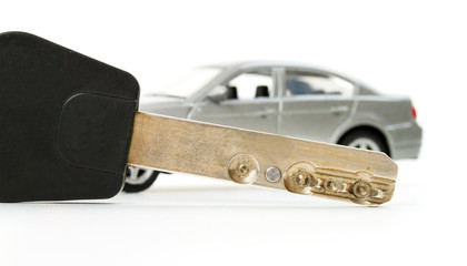Key and little toy car in blur isolated on white background
