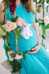 Portrait of a pregnant woman on a swing in the room