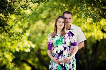 Beautiful pregnant woman with her husband in sunny park