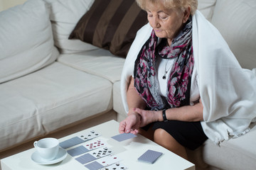Senior woman playing cards alone