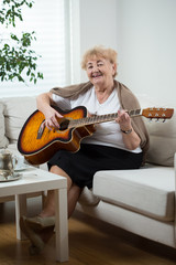 Elderly woman playing the guitar