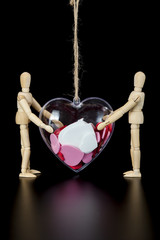 Wooden dummies hold heart on string
