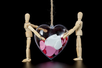 Wooden dummies carry heart on string