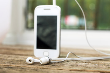 White smart phone with earphones and isolated screen on old wood