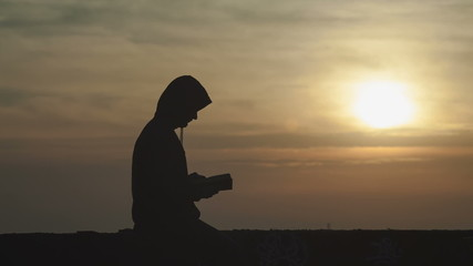 A man dies hard, reading a book on a background sunset