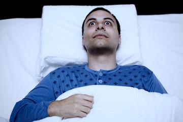 Portrait of an insomniac man trying to sleep