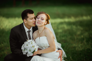 the bride and groom sit in the park and petting