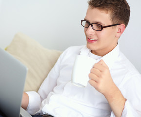 Relaxed attractive man holding coffee while working on his