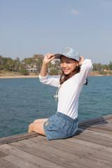 portrait of beautiful woman happy face sitting on wood port sea