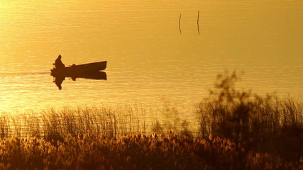 Small boat on the lake in sunset light