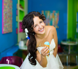 Young beautiful bride having an ice cream in cafe