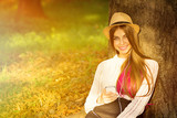 Boho styled teenage girl with smartphone in park in summer poster
