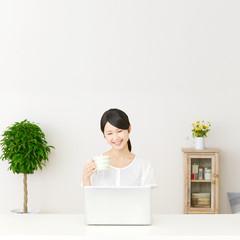 パソコンの前に座って笑う女性