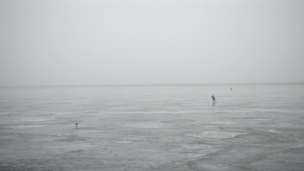 Winter fisherman making hole in ice with an ice chisel