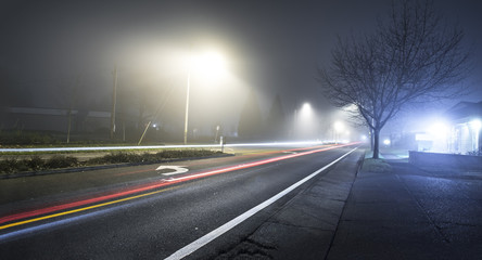Road at night with fog and long exposure of car trail