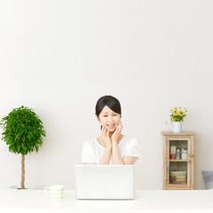 パソコンの前に座って困る女性