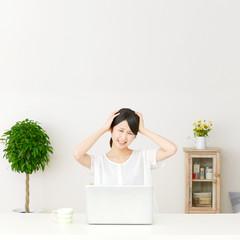 パソコンの前に座って頭を抱える女性