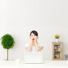 パソコンの前に座って驚く女性