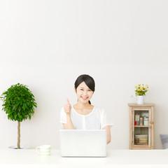 パソコンの前に座ってグッドサインする女性