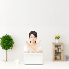 パソコンの前に座ってバツ印する女性