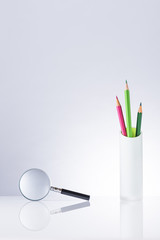 Pencils and Magnifier.On blank desk.