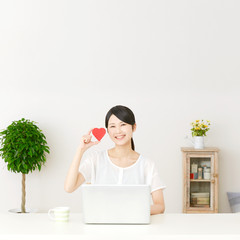 パソコンの前に座ってハートを持つ女性