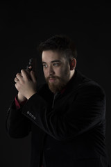 Goatee Man in Black Suit Holding Weapon