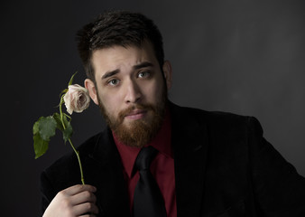 Serious Man in Formal Attire Holding Rose