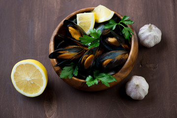 Steamed mussels with parsley, lemon and garlic, high angle view