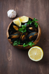 Boiled mussels in a wooden bowl over dark wooden surface