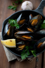 Boiled mussels with parsley, lemon and garlic in a frying pan